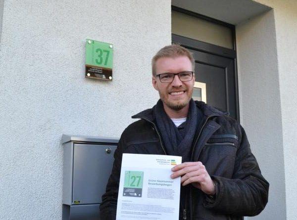 Klimaschutzmanager Stephan Griesehop mit dem Bewerbungsbogen vor einem bereits 2017 mit der Grünen Hausnummer ausgezeichneten Wohnhaus. Foto: Landkreis Grafschaft Bentheim