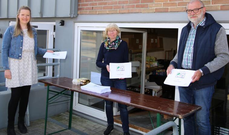 Harens Gleichstellungsbeauftragte Christin Jönen übergibt Marianne Ströer und Jan Krüssel von der Harener Tafel (v.l.) die Malhefte. Foto: Stadt Haren (Ems).