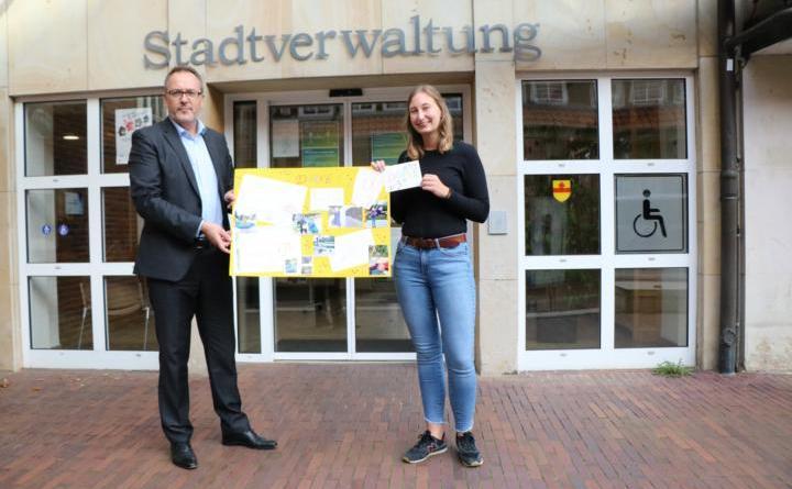 Bürgermeister Helmut Knurbein (links) und Sandra Thien, Jugend- und Kulturzentrum JAM (rechts) freuen sich über das selbst gestaltete Plakat der Holthausener Kids. Foto: Stadt Meppen -