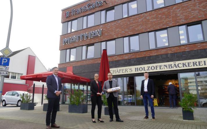 """Dietmar Lager (rechts), Wirtschaftsförderung der Stadt Lingen, und Albert Bröskamp (links), Eigentümer des Gebäudes, begrüßen Yvonne und Jürgen Baars mit ihrem Unternehmen """"TransGate"""" in den neuen Räumlichkeiten. Foto: Stadt Lingen"""