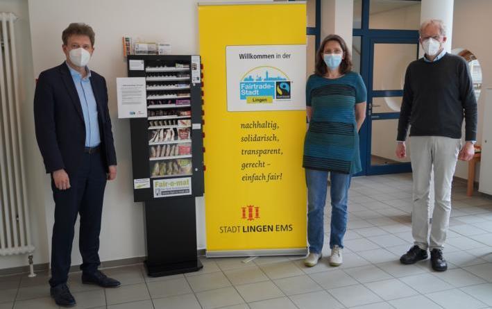 Oberbürgermeister Dieter Krone, Uta van Roje (Vorsitzende Weltladen Lingen) und Holger Berentzen (Sprecher Fairtrade-Steuerungsgruppe) testen den neuen Fair-o-mat im Foyer des Neuen Rathauses. Foto: Stadt Lingen