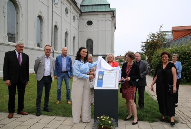Ehrengast Gitta Connenmann und die Gleichstellungsbeauftragte der Stadt Haren (Ems) (links und rechts neben der Tafel) nahmen die Enthüllung der Gedenktafel vor. Die Projektbeteiligten aus Politik und Arbeitskreis sahen dabei zu. Foto: Stadt Haren (Ems). Foto: Stadt Haren (Ems)