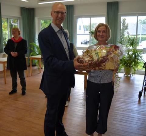 Bürgermeister Helmut Höke überreicht einen Präsentkorb zum Start des Mittagstisches in Dalum an Initiatorin Gertrud Lüken. Foto: Gemeinde Geeste