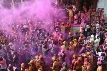 TOPSHOT - Indian Hindu devotees celebrate Holi, the spring festival of colours, during a traditional gathering at Nandgaon village in Uttar Pradesh state on March 7, 2017. Holi is observed in India at the end of the winter season on the last full moon of the lunar month, and will be celebrated on March 13 this year. / AFP PHOTO / - (Photo credit should read -/AFP/Getty Images)