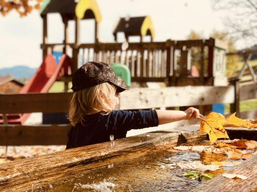 Merlin spielt mit Wasser auf dem Spielplatz