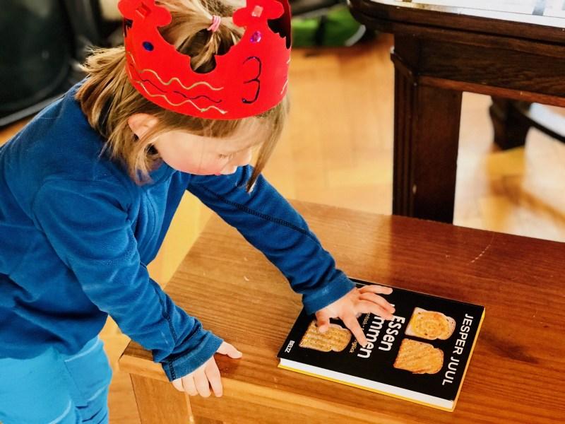 Familienglück am Familientisch – Merlin liest den Titel des Buchs Essen kommen von Jesper Juul