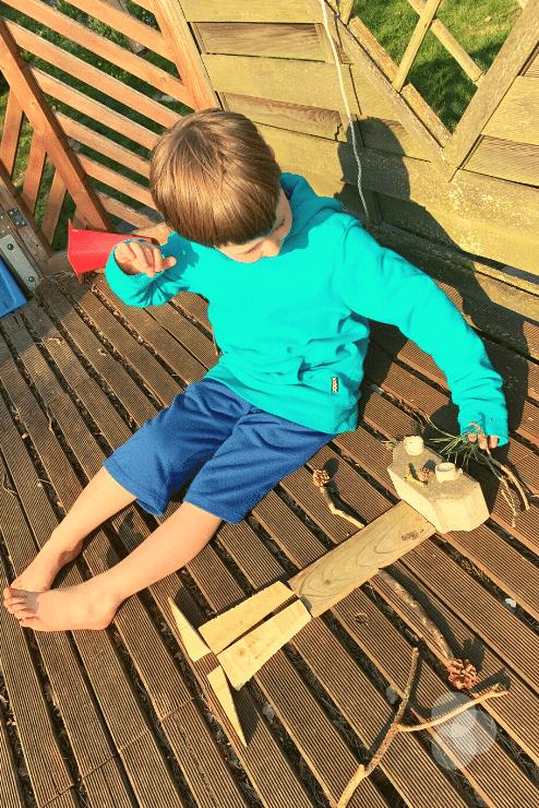 Rückblick – Merlin legt Oma aus Holz, Steinen und Blumen