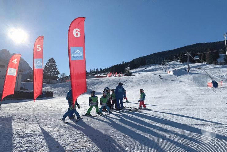 Kinder auf der Piste mit Skilehrer