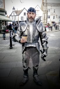 Man promoting Glastonbury Medieval Fair in full armour with a takeaway cup of coffee in Glastonbury Town