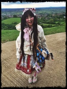 Japanese girl in bright hippy clothes on Glastonbury Tor.