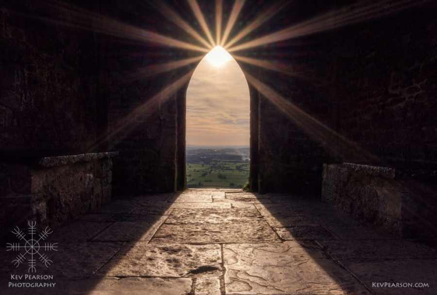Divine Light by Kev Pearson. The sun trhought the archway of the tower on Glastonbury Tor.