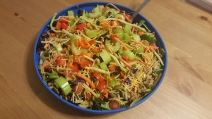 A huge bowl of fresh vegetables cut into a salad