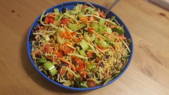 A huge bowl of fresh vegetables cut into a salad
