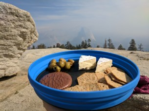 A plate with brie cheese, crackers, green olives and chocolate cookies with Half Dome in the background seen from Sentinel Dome in Yosemite National Park