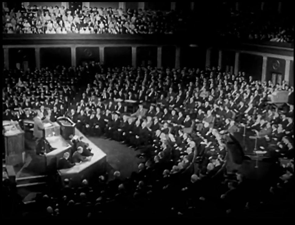 Scene from video for Box of Tricks - politician addressing audience