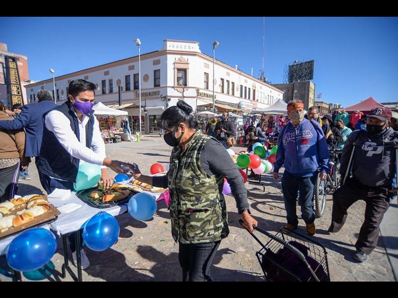 Personas reciben un trozo de rosca en el Centro, en el Día de los Reyes Magos