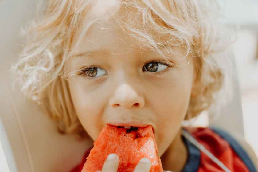 close up photo of boy eating watermelon