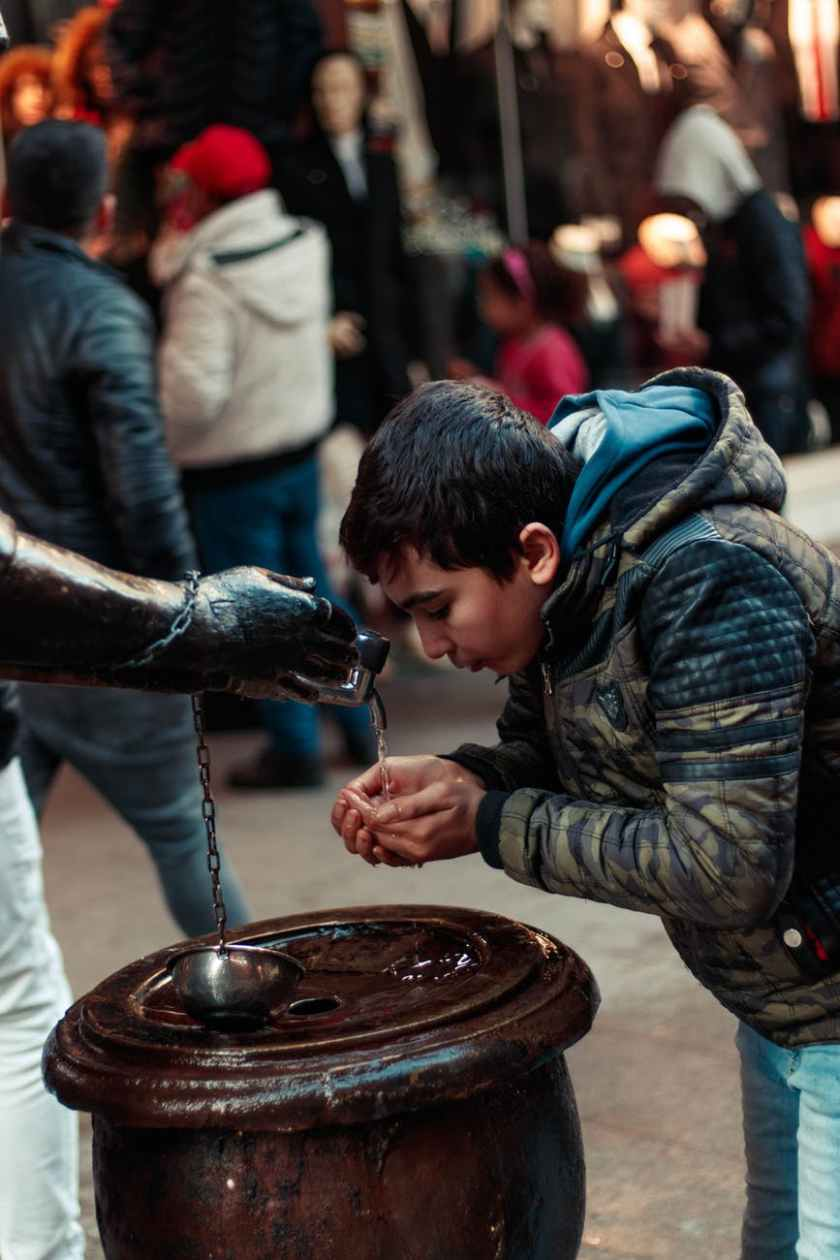 boy drinking water on a fountain