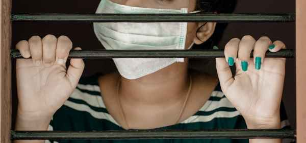 woman in green and white stripe shirt covering her face with white mask