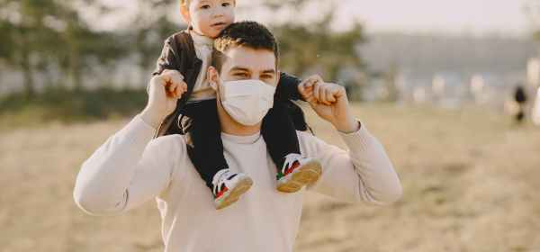 man in white long sleeve shirt carrying baby on his back