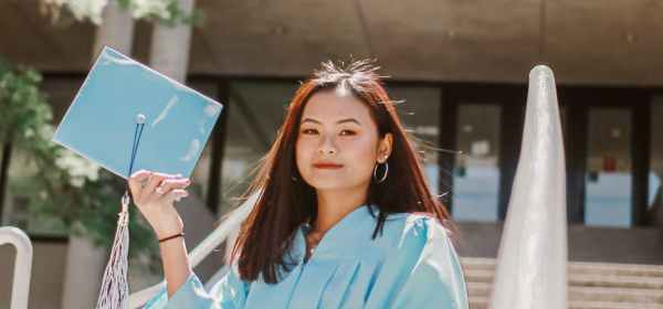 photo of woman in blue academic dress smiling