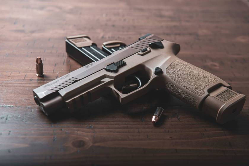 black and silver semi automatic pistol on brown wooden table