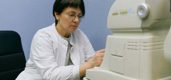 female ophthalmologist working with autorefkeratometer in doctor office