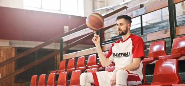 professional concentrated basketball player spinning ball on finger
