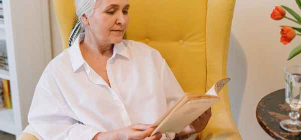 an elderly woman sitting on a couch reading a book