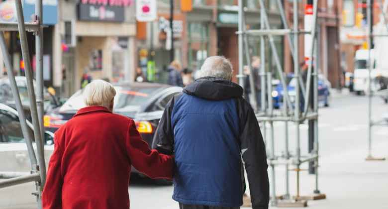 anonymous elderly couple holding hands and strolling in city