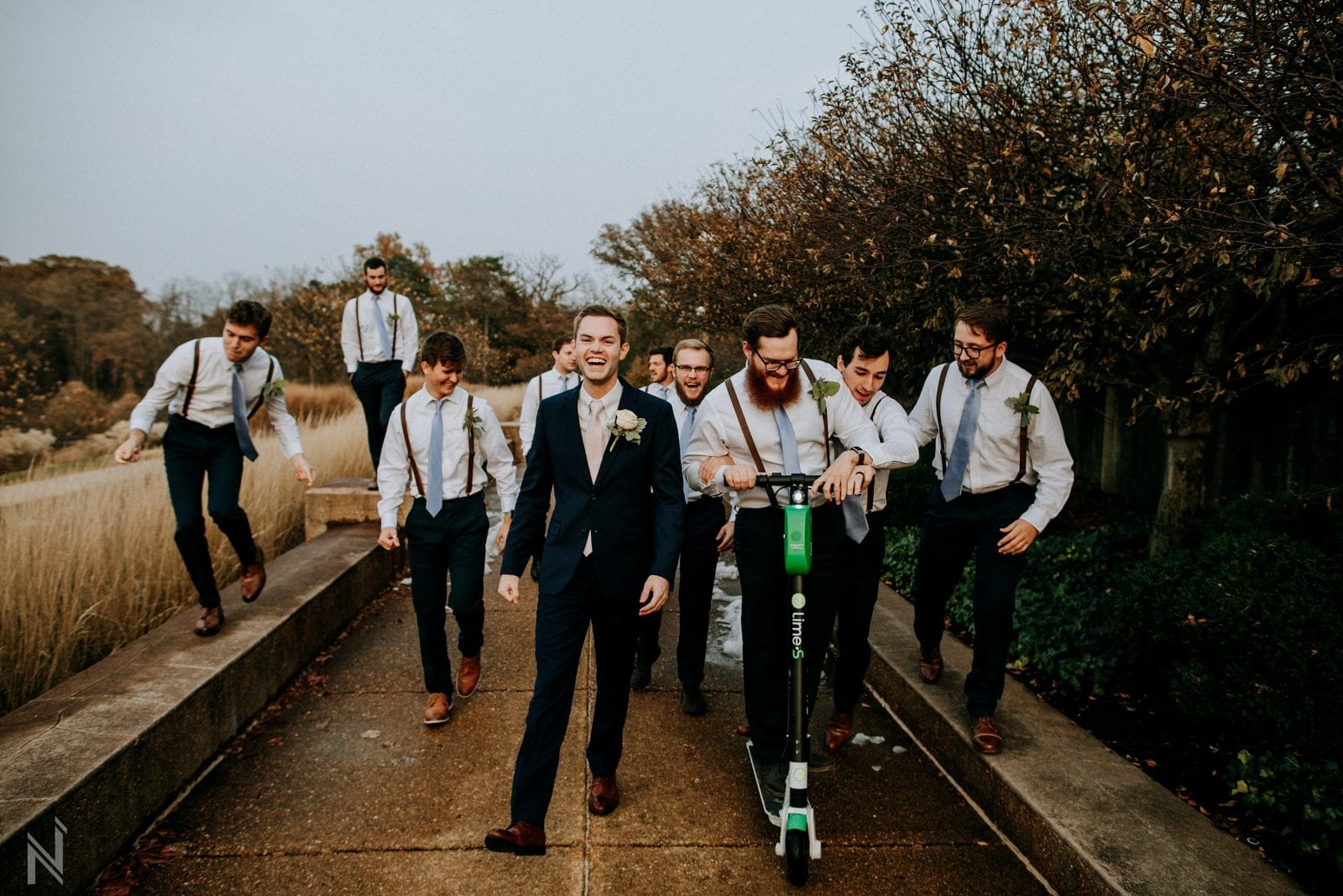 Funny groomsmen limebike scooter picture at worlds fair pavilion in Forest Park in St. Louis, Missouri