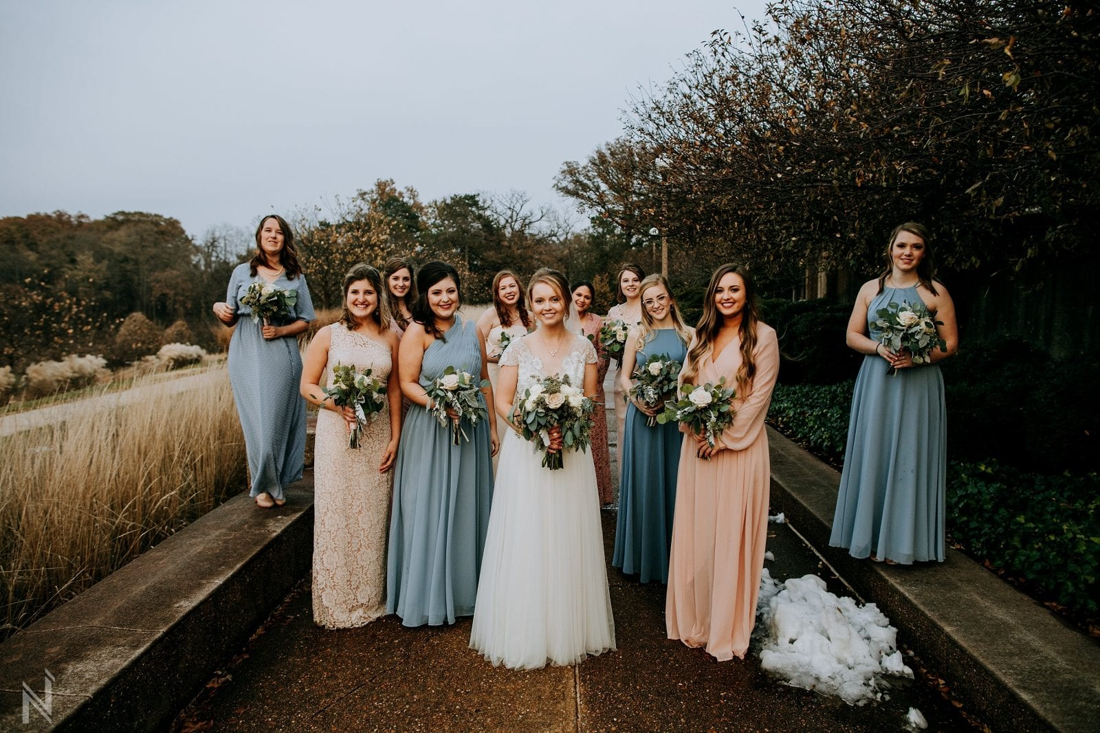 Wedding party with different colored bridesmaid dresses at worlds fair pavilion in Forest Park in St. Louis, Missouri