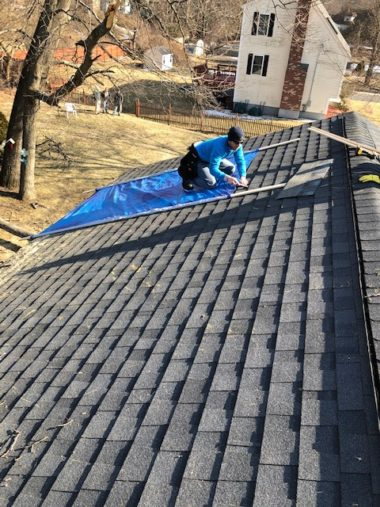 Roofer covering damaged roof for an emergency roof repair
