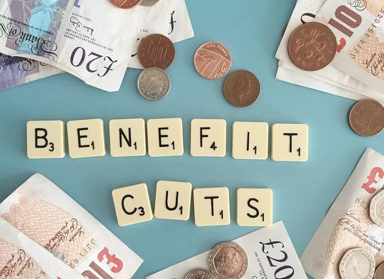 some money with the words benefit cuts