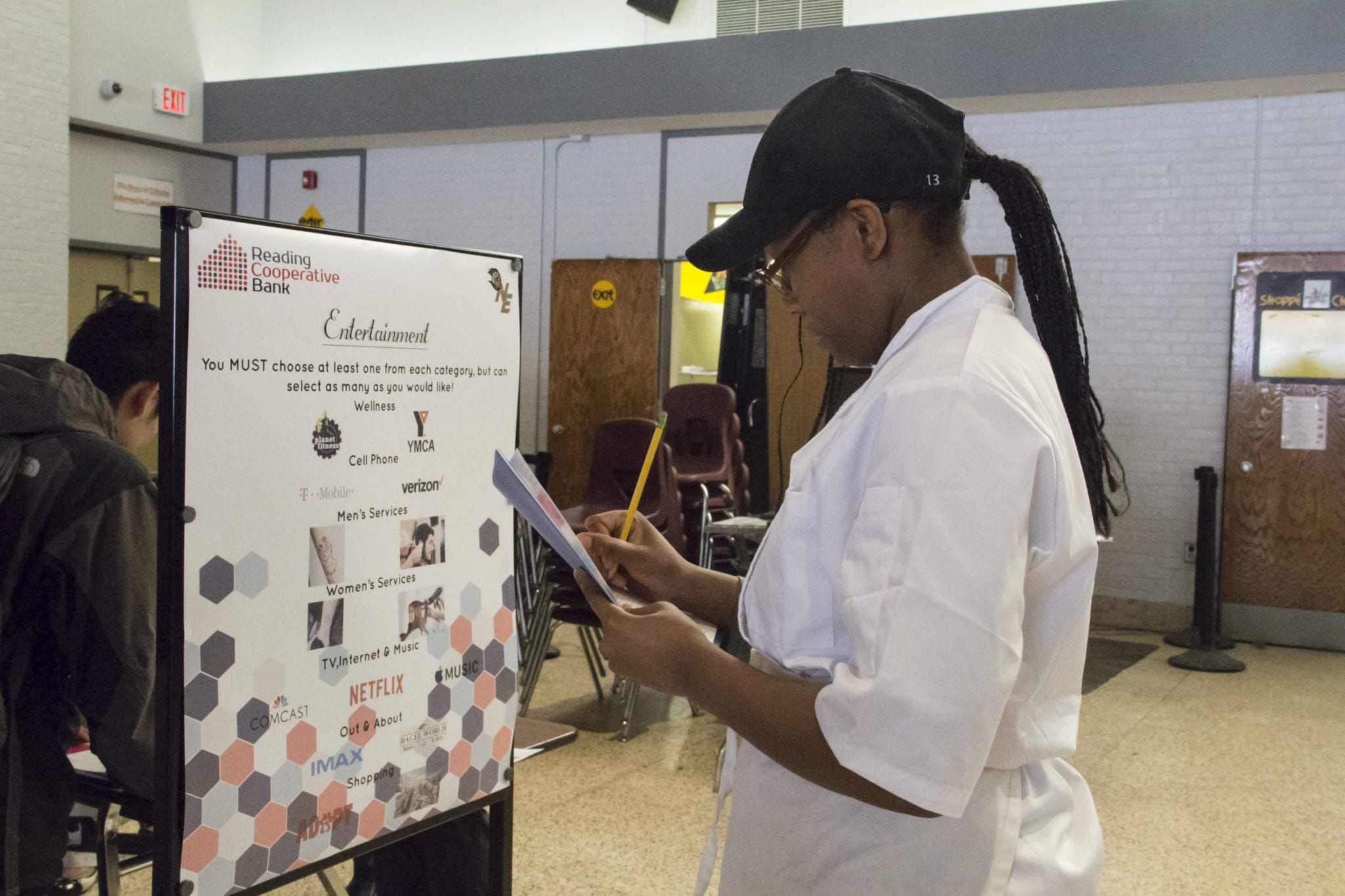 Malden resident Trinitee Arnold, a junior from the culinary shop, fills out her form at the entertainment section of the financial literacy fair. (Courtesy Photo Northeast Metro Tech)