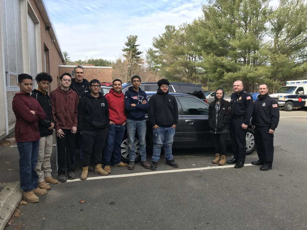 Left to right: Erick Menjivar Mejia, of Chelsea, Jorge Benavides Chavez, of Revere, Andrew O'Neil, of Chelsea, automotive technology instructor Robert MacGregor, Juan Valasquez Restrepo, of Chelsea, Luis Barillas, of Chelsea, Christopher Mendez, of Chelsea, Jay Martinez, of Chelsea, Payten Kiley, of Melrose, Reading Police Chief Mark Segalla and Reading Police Armorer Patrick Dawley. (Courtesy Photo Reading Police Department)