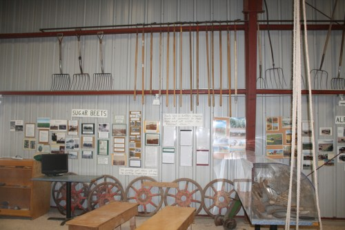 A string of farm tools act not only as a museum display, but also a form of decoration over a series of information cards about beet farming.