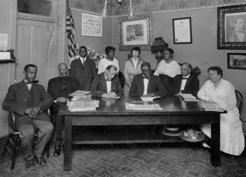 """Group photograph of early NAACP members taken in Dr. Clarence Holme's office in Denver. Caption on back says """"Dr. Holmes Office: Denver. NAACP Meeting? 3rd from Left (Seated) Dr. Westbrook, 2nd from Left (Standing) Mary E Holmes."""" (Photo from the Denver Public Library Archive.)"""