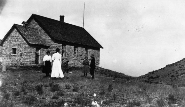 "The school house in Stout. The text attached to the photo states, ""Schoolchildren and their teacher, Nora Wathen, stand outside their one-room native stone schoolhouse, Stout (also known as Petra), Colorado in Larimer County."" (Call # X-13709)"