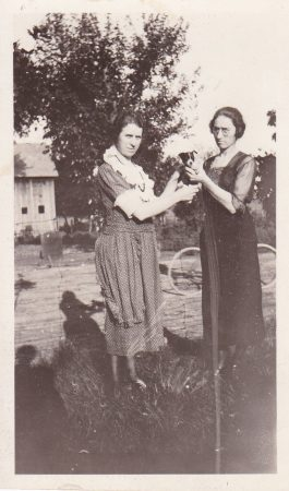 Grace Day (at right) is holding a puppy as she stands with her sister, Mabel Paine. I don't know how anyone could be holding such a cute puppy and not smiling, but Grace doesn't smile much in any of her pictures.