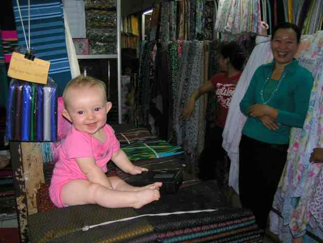 Baby Penny sitting on silks in Cambodia