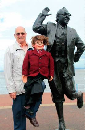 Mike with Charlie, Eric's old ventriloquist's dummy, next to Eric's statue at Morecambe
