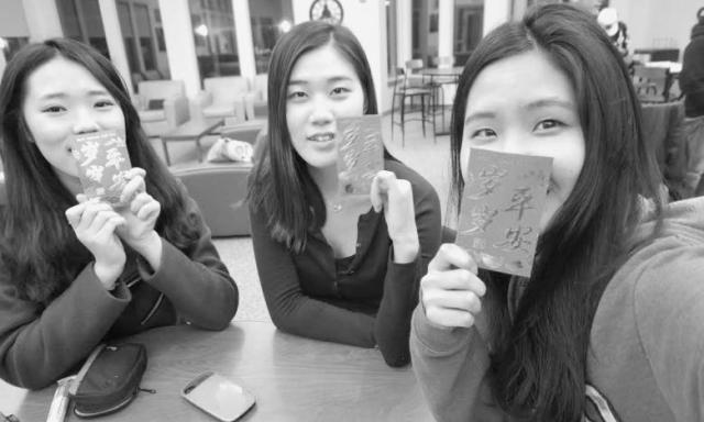 three students holding up cards