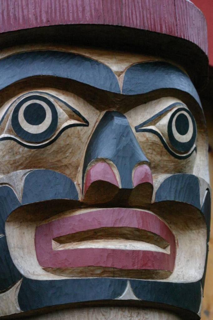 The carved face of a totem pole. The negative space is unpainted red, and the facial features are painted red and black.