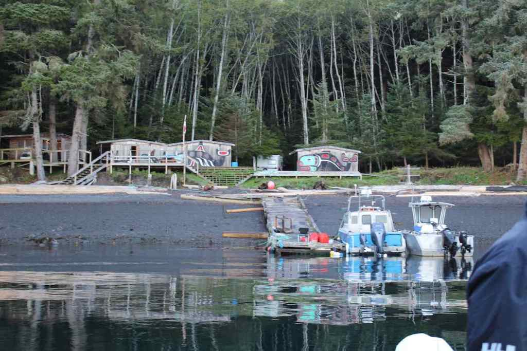 The ocean is in the foreground, and there are two boat moored to the right and two small wooden house stand in the background in front of a forest of evergreen trees.
