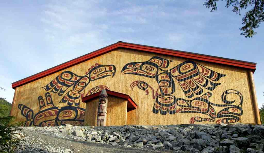 The front of a wooden long house with four animals (two birds and two mammals) painted in red and black on either side of the door. There is also a wooden sculpture in the center. There is a rocky road in front and a blue sky behind.