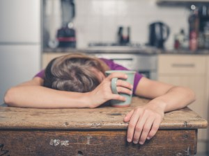 tired woman resting her head on the table