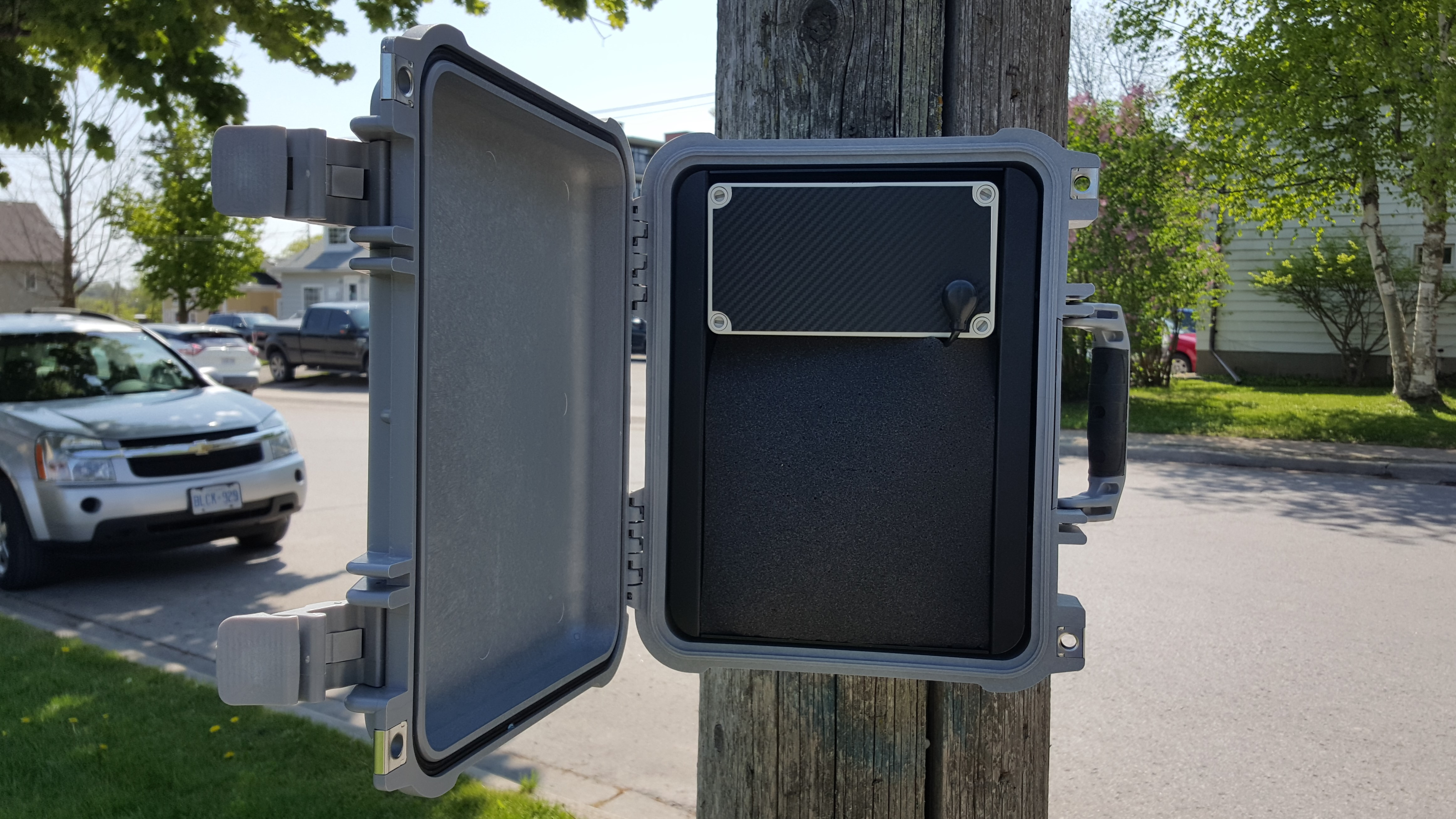 Black CAT radar unit affixed to a utility pole, detecting vehicles on community road.