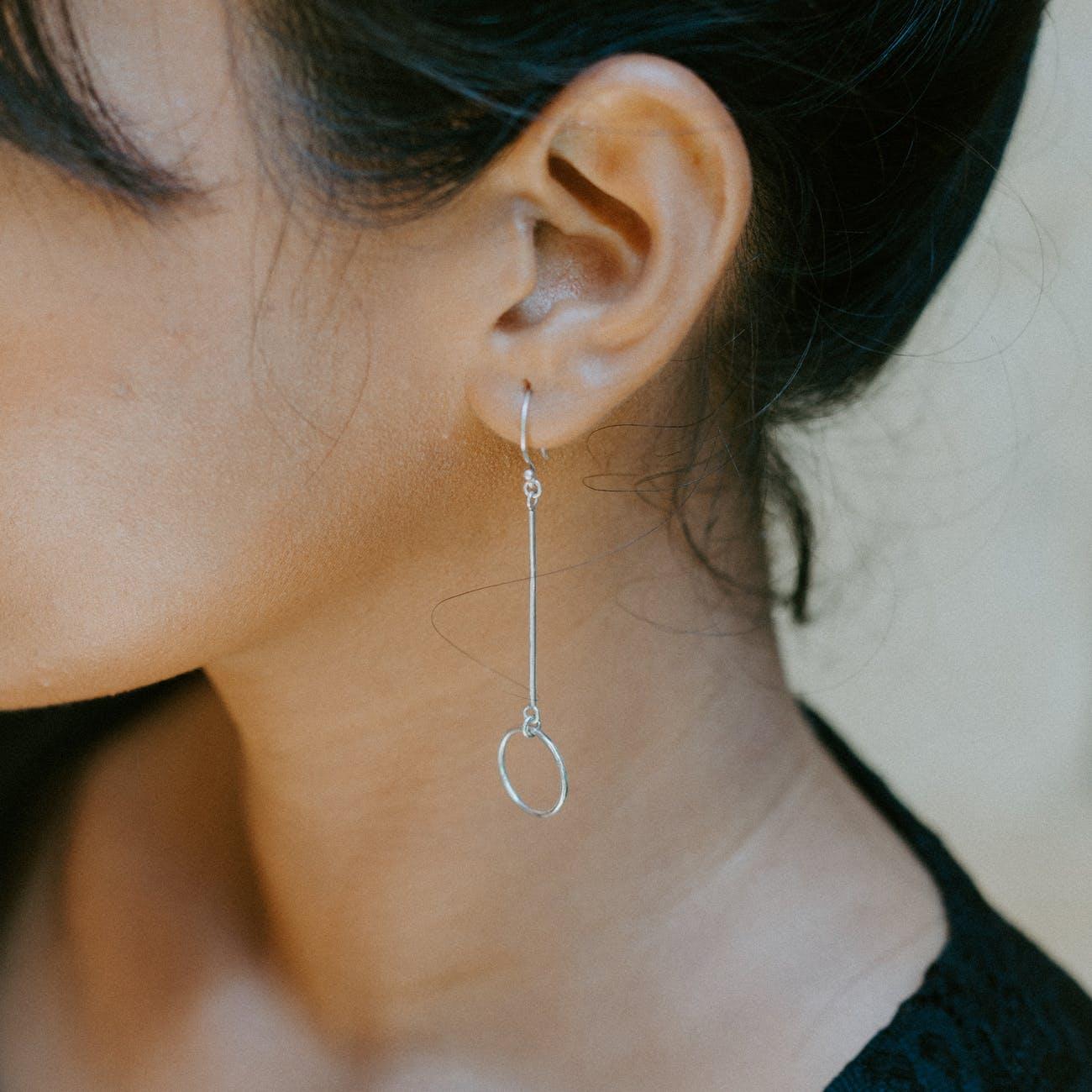 woman wearing silver colored earrings after ear piercing