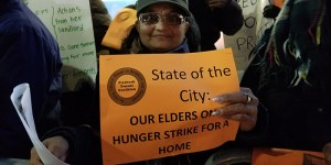 "Woman holds a Flatbush Tenant Coalition sign saying ""State of the City: Our Elders On Hunger Strike for a Home"""